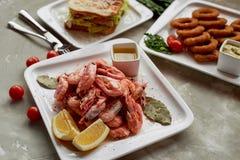 在客栈或酒吧的啤酒快餐 虾、味道好的三明治和金黄洋葱圈 免版税库存照片