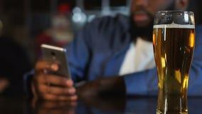 在客栈,饮用的啤酒和聊天的非裔美国人的人消费时间在电话 影视素材