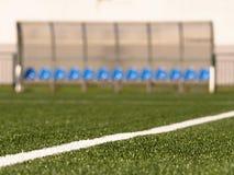 在室外体育场球员的新的蓝色塑料位子换下场,椅子在透明塑料屋顶下 免版税库存图片