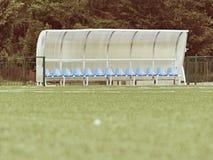 在室外体育场球员的新的蓝色塑料位子换下场,椅子在透明塑料屋顶下 免版税图库摄影