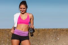 在室外体育的健身房以后的妇女饮用水 免版税库存照片