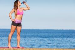 在室外体育的健身房以后的妇女饮用水 免版税图库摄影