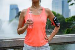 在室外健身锻炼期间的妇女饮用水 免版税图库摄影