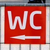 在室外区域的红色标志在与白色书面标志&#x22的一个节日; WC'并且指向往洗手间的箭头 免版税库存图片