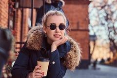 在室外咖啡馆的一份美丽的年轻女人饮用的咖啡 库存照片