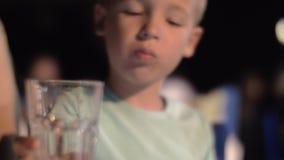 在室外咖啡馆的乏味男孩饮用水在晚上 股票录像