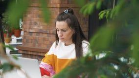 在室外咖啡馆的白种人妇女用途膝上型计算机 股票视频