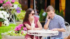 在室外咖啡馆的年轻夫妇 因为他是繁忙的与差事,女孩对她的男朋友是恼怒 影视素材