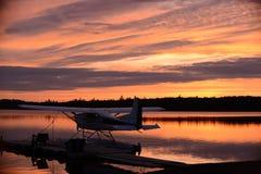 在室外撤退的日落与在湖的一架水上飞机 免版税图库摄影