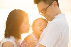 在室外日落海滩的亚洲家庭 免版税库存照片