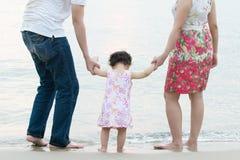 在室外沙子海滩的愉快的亚洲家庭 免版税库存照片