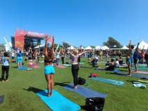 在室外瑜伽类期间,人们举胳膊在头顶上 免版税图库摄影
