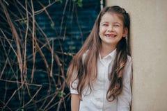 在室外的墙壁附近的小和逗人喜爱的女孩逗留 库存图片