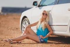 在室外的汽车附近的美丽的年轻性感的妇女 免版税库存图片