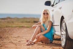 在室外的汽车附近的美丽的年轻性感的妇女 免版税图库摄影