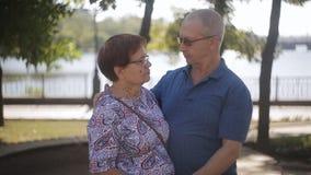 在室外的爱的愉快的年长夫妇 愉快的年长前辈夫妇在晴朗的庭院里 影视素材