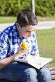 读在室外的Happiness.Young人一本书用黄色苹果。 免版税库存照片