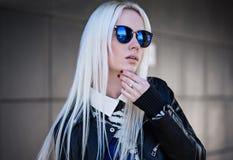 在室外的sunglassses的白肤金发的模型 免版税库存图片