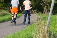 在室外锻炼的年轻夫妇与轴向溜冰者 免版税库存照片