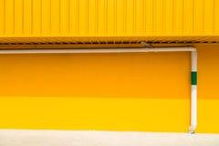 在室外黄色的墙壁上的白色管子 免版税库存图片