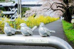 在宫城, Tohoku,日本金属化与可爱的鸟雕塑的障碍在沿城石河岸的边路在春天 免版税库存图片