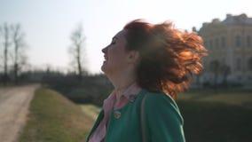 在宫殿和它前面的年轻女人跳舞是运河在面带绿色时尚夹克和微笑的太阳下 股票录像