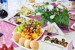 在宴会的服务的桌 果子、快餐、纤巧和花在餐馆 庄严的事件或婚礼 免版税库存图片
