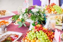 在宴会的服务的桌 果子、快餐、纤巧和花在餐馆 庄严的事件或婚礼 库存图片