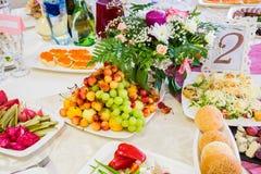 在宴会的服务的桌 果子、快餐、纤巧和花在餐馆 庄严的事件或婚礼 免版税库存照片
