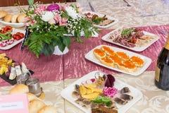 在宴会的服务的桌 饮料、快餐、纤巧和花在餐馆 节日庆典或婚礼 免版税图库摄影