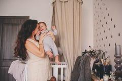 在家一起使用愉快的母亲和小拿着和亲吻她的儿子,妈妈11个月大男孩 库存照片