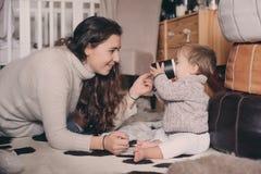 在家一起使用母亲和小的儿子 喝的教的婴孩从杯子 系列父亲女孩愉快的生活方式一点 图库摄影