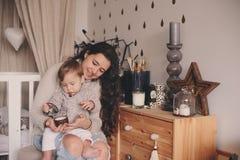 在家一起使用母亲和小的儿子 喝的教的婴孩从杯子 系列父亲女孩愉快的生活方式一点 免版税库存图片