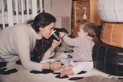 在家一起使用母亲和小的儿子 喝的教的婴孩从杯子 系列父亲女孩愉快的生活方式一点 免版税库存照片