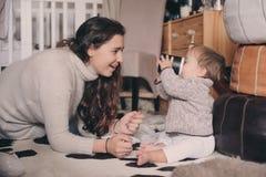 在家一起使用母亲和小的儿子 喝的教的婴孩从杯子 系列父亲女孩愉快的生活方式一点 免版税图库摄影