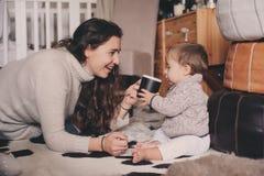 在家一起使用母亲和小的儿子 喝的教的婴孩从杯子 系列父亲女孩愉快的生活方式一点 库存图片