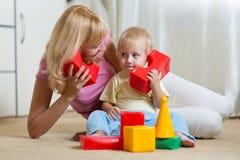 在家一起使用逗人喜爱的母亲和儿童男孩的角色 免版税库存照片