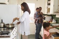 在家一起准备膳食的家庭在厨房里 库存图片