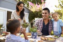在家一起吃室外膳食的家庭在庭院里 免版税库存照片