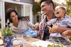在家一起吃室外膳食的家庭在庭院里 库存照片
