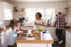 在家一起吃早餐的家庭在厨房里 免版税库存图片