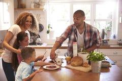 在家一起吃早餐的家庭在厨房里 库存图片