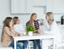 在家一起坐在厨房里的愉快的女同性恋的家庭,所有在便服 免版税库存照片