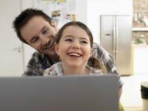 在家一起微笑的父亲和的女儿有膝上型计算机的 免版税库存照片