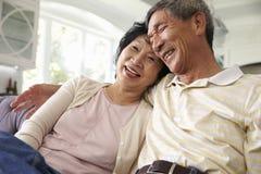 在家一起放松在沙发的资深亚洲夫妇 库存照片