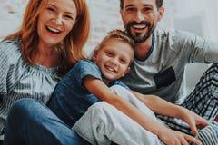 在家一起放松愉快的微笑的家庭 免版税图库摄影