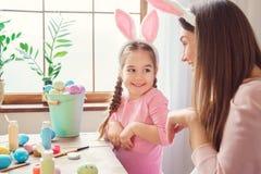 在家一起母亲和女儿在演奏兔子的兔宝宝耳朵的复活节准备 免版税图库摄影