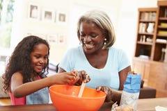 在家一起烘烤的祖母和的孙女 免版税图库摄影