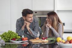 在家一起烹调在厨房里的愉快的年轻夫妇画象  免版税库存照片