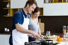在家一起烹调在厨房里的愉快的年轻夫妇 免版税图库摄影